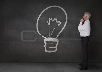 Doubtful businessman looking at a light bulb