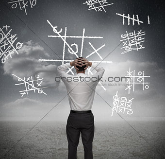 Anxious businessman losing at noughts and crosses