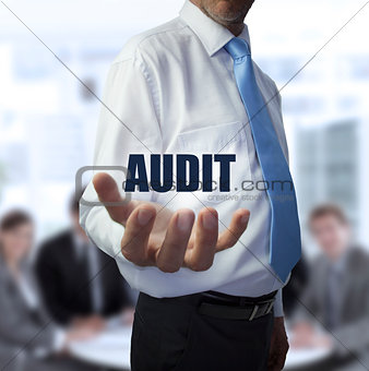 Elegant businessman holding the word audit