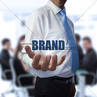 Smart businessman holding the word brand