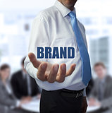 Elegant businessman holding the word brand