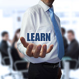 Smart businessman holding the word learn