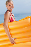 Smiling woman holding air mattress