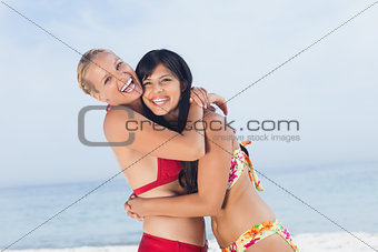 Friends hugging and smiling at camera