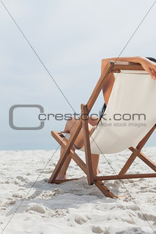 Woman resting on her deck chair in front of ocean