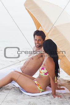 Couple speaking together on beach towel