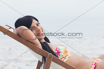 Smiling woman resting on deck chair