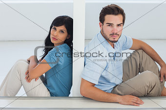 Unhappy couple are separated by white wall