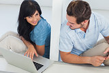 Smiling woman showing something on laptop at her boyfriend