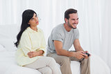Annoyed woman looking up during her boyfriend playing video games
