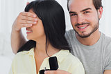 Smiling man about to propose hiding eyes of his girlfriend