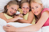 Woman napping in bed with her cute children