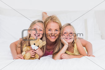 Portrait of woman in bed with her children