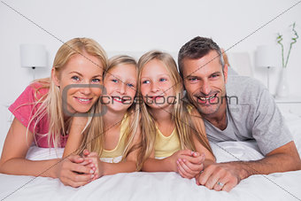 Portrait of parents lying in bed with their children