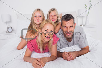 Portrait of parents lying in bed with their twins