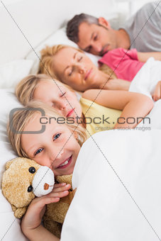 Young girl awake next to her sleeping family