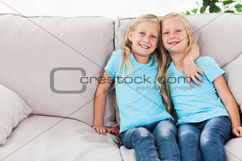 Blonde twins sitting on a couch
