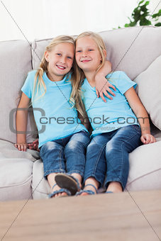 Cute twins sitting on a couch