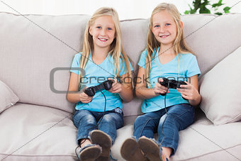 Portrait of twins playing video games together