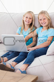 Cute twins using a laptop together