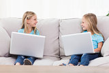 Cute twins using laptops sitting on a couch