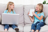 Young twins using a laptop and a tablet sitting on a couch