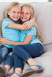 Young twins embracing each other on a couch