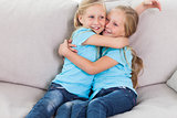 Young twins embracing each other sitting on a couch