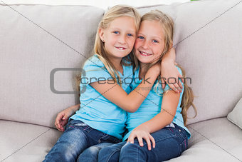 Cute twins embracing each other sitting on a couch