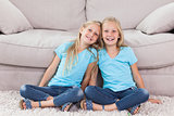 Twins sitting on a carpet