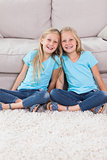 Young twins sitting on a carpet