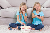 Twins eating popcorn and watching television