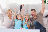 Twins and parents raising arms while watching television
