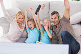 Cute twins and parents raising arms while watching television