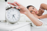 Woman turning off the alarm clock in the morning
