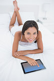 Woman using her tablet lying in bed
