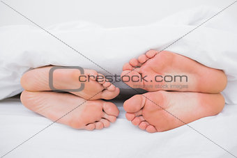 Feet of a couple face to face in bed