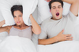 Woman covering ears with a cushion while her partner is snoring