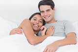 Woman embracing her partner in bed