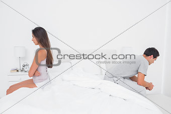 Couple sulking each other sitting on bed