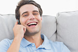 Man laughing while having a phone conversation