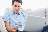 Man using his credit card to purchase online