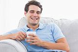 Portrait of a cheerful man holding a cup of coffee