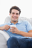 Portrait of a smiling man holding a cup of coffee