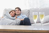 Beautiful couple resting on a couch with flutes of champagne