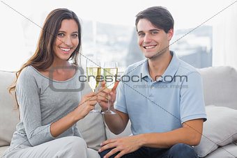 Portrait of lovers clinking their flutes of champagne