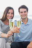 Portrait of a couple toasting their flutes of champagne