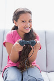 Little girl playing video game on sofa