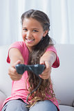 Smiling little girl playing video game on sofa