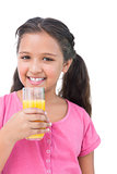 Happy little girl drinking orange juice